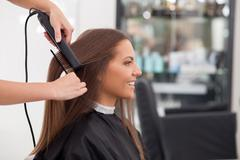 Experienced young hairstylist is serving her customer Stock Photos