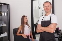 Cheerful young hairstylist is serving his customer Stock Photos