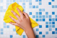 Cheerful maid is cleaning tiled surface with a wisp Stock Photos