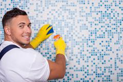 Attractive young cleaner is washing wall with a wisp Stock Photos