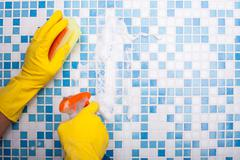Skilled washer is cleaning his house with sponge and spray Stock Photos