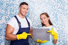 Attractive cleaners are cleaning a house with fun - stock photo