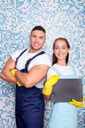 Cheerful young workers are doing clean-up in bathroom Stock Photos