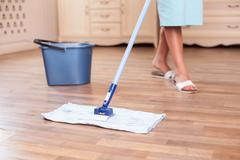 Skilled young housewife is cleaning floor with a mop Stock Photos