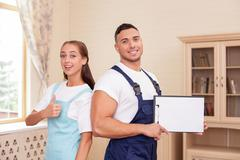 Attractive young workers in apron are cleaning the house Stock Photos