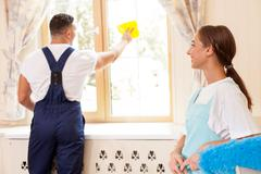 Cheerful young cleaners are cleaning a house together Stock Photos