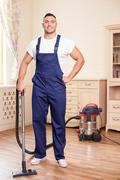 Attractive young man is cleaning flooring in a house Stock Photos