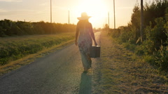 Young woman walking on country empty road at the sunset Stock Footage