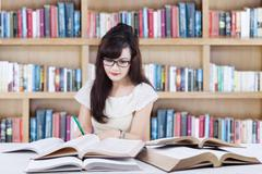 Attactive learner doing school task in library Stock Photos