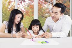 Creative child studying with parents at home Stock Photos