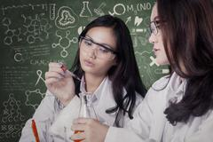 Female students doing research together in lab - stock photo