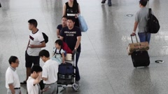 Chinese family walking at Shanghai HOngqiao airport departure hall for holiday Stock Footage