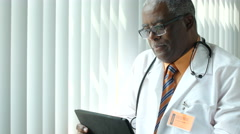 Black male Doctor looking at his ipad/tablet - stock footage