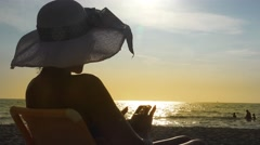 Sea sunset with young woman with sun hat using cellphone while sitting on sun Stock Footage