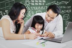 Two parents teach their child in the class - stock photo