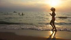 Young sport woman with hat is engaged in gymnastics at sea at sunrise, sunset Stock Footage