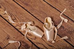 Ballet pointe shoes lie on wooden floor. - stock photo