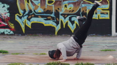 Slow motion Female Break Dancer Performing in front of Graffiti Wall Stock Footage