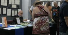 4K Stanton T. Friedman Ufologist nuclear physicist signing book in  UFO festival Stock Footage