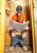 Man in respirator reading newspaper in wooden village WC Stock Photos