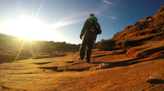 Man hiking over sandstone toward the sun. Stock Footage