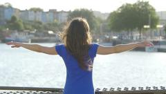 Young woman open her arms in front of the river Stock Footage