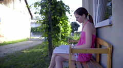 Mailman bring newspaper to woman sitting on bench 4K Stock Footage