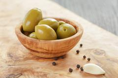 green huge olives on wood table - stock photo