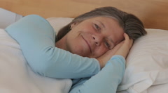 woman in her 50s lying in bed and is smiling at the camera - stock footage