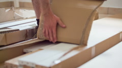 Stock Video Footage of Ripping apart long cardboard box on floor