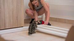 Kitten helping woman screwing wooden parts Stock Footage