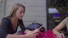 Cute girls use cell phones together - stock footage