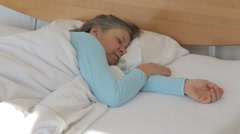 woman in her 50s sleeping in bed restless - stock footage