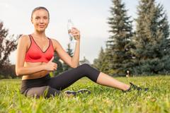 Attractive young sportswoman is drinking aqua after exercising Stock Photos