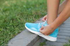 Young woman is fixing laces of her running shoes - stock photo