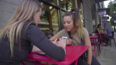 Friends use cell phone at coffee shop Stock Footage