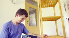 Clumsy worker fall while screwing a shelf tower 4K - stock footage