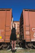 Woman Standing with Railroad Boxcars - stock photo