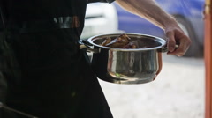 Person hold pot with roasted meat close up Stock Footage