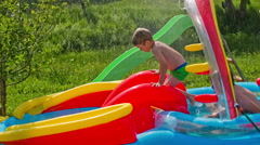 Kid sliding down on inflatable water pool Stock Footage