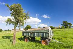 An old fertilizer trailer on a green meadow with a village in the background  Stock Photos