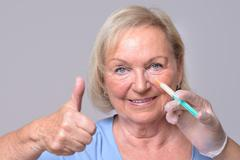 Satisfied Woman with Injection on Face Stock Photos