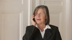 businesswoman in her 50s talking on the phone and looks cheerful - stock footage