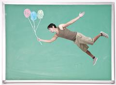 Stock Photo of Man Floating with Chalk Balloons