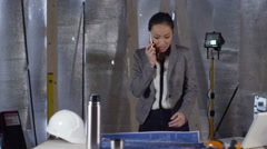 4k Female engineer or architect talking on phone and looking at plans - stock footage