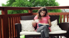 Girl drinking coffee and reading book on the deck Stock Footage