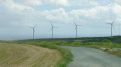 Stock Video Footage of Abandoned road near modern windmills rotating on wind farm. Future technology