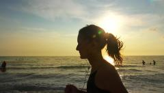 Running fit girl with horsetail and earphones relaxing jogging on summer beac Stock Footage
