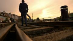Lonely man walking in the middle of an old railway Stock Footage