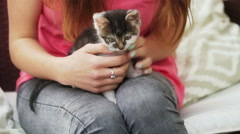 Girl holding kitty on her knees and sitting on patio Stock Footage